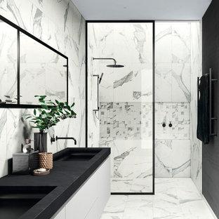 Immagine di una stanza da bagno padronale minimalista di medie dimensioni con doccia a filo pavimento, pistrelle in bianco e nero, piastrelle in gres porcellanato, pareti nere, pavimento in gres porcellanato, lavabo da incasso, pavimento bianco e doccia con tenda