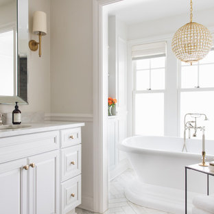 Immagine di una stanza da bagno chic con ante con bugna sagomata, ante bianche, pareti beige, lavabo sottopiano, pavimento bianco e top bianco