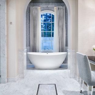 Imagen de cuarto de baño principal, tradicional, con bañera exenta, armarios con paneles lisos, puertas de armario blancas, baldosas y/o azulejos grises, paredes multicolor y suelo de mármol