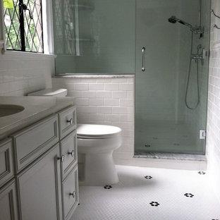 Idéer för ett litet klassiskt badrum, med luckor med infälld panel, vita skåp, bänkskiva i akrylsten, vit kakel, keramikplattor, en dusch i en alkov, en toalettstol med separat cisternkåpa, ett undermonterad handfat, vita väggar och mosaikgolv