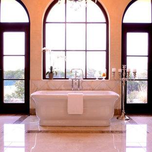 Ispirazione per un'ampia stanza da bagno padronale chic con lavabo sottopiano, ante con bugna sagomata, ante in legno bruno, top in onice, vasca freestanding, doccia alcova, WC monopezzo, piastrelle beige, piastrelle in pietra, pareti beige e pavimento in marmo