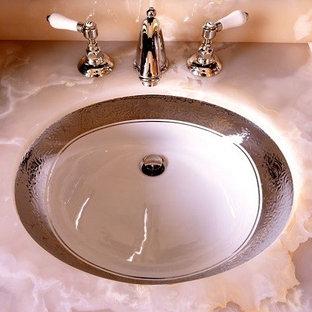 Inredning av ett klassiskt mycket stort en-suite badrum, med ett undermonterad handfat, luckor med upphöjd panel, skåp i mörkt trä, bänkskiva i onyx, ett fristående badkar, en dusch i en alkov, en toalettstol med hel cisternkåpa, beige kakel, stenkakel, beige väggar och marmorgolv