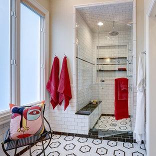 Klassisk inredning av ett en-suite badrum, med vit kakel, tunnelbanekakel, mosaikgolv, en dusch i en alkov, beige väggar, flerfärgat golv och dusch med gångjärnsdörr