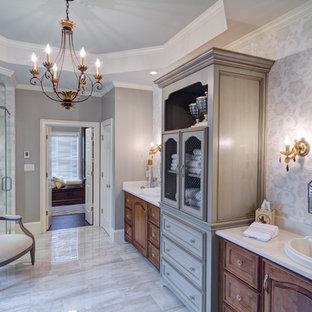 Example of a large classic master gray tile and stone tile porcelain floor and gray floor bathroom design in Atlanta with a drop-in sink, furniture-like cabinets, medium tone wood cabinets, quartzite countertops, gray walls and a hinged shower door