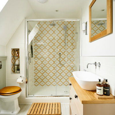 Inspiration for a small timeless master multicolored tile and ceramic tile ceramic tile and beige floor bathroom remodel in Sussex with flat-panel cabinets, beige cabinets, a one-piece toilet, white walls, a trough sink, wood countertops and beige countertops