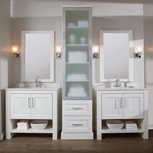 Esempio di una stanza da bagno padronale tradizionale di medie dimensioni con lavabo sottopiano, ante lisce, ante bianche, top in superficie solida, piastrelle bianche, pavimento in legno massello medio, pareti bianche, pavimento marrone e top bianco