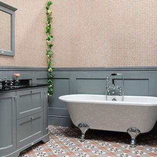 Idee per una grande stanza da bagno chic con consolle stile comò, ante grigie, vasca freestanding, piastrelle rosa, piastrelle a mosaico, pareti grigie, pavimento in gres porcellanato, top in marmo, pavimento multicolore e top nero