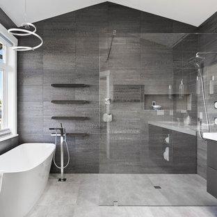 Diseño de cuarto de baño principal, contemporáneo, grande, sin sin inodoro, con armarios con paneles lisos, puertas de armario negras, bañera exenta, baldosas y/o azulejos grises, baldosas y/o azulejos azules, baldosas y/o azulejos de porcelana, paredes grises, suelo de baldosas de porcelana, lavabo bajoencimera, encimera de cuarzo compacto, suelo gris, ducha abierta y encimeras blancas