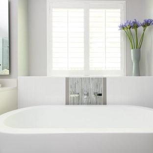 Modelo de cuarto de baño principal, actual, de tamaño medio, con lavabo encastrado, armarios con paneles lisos, puertas de armario amarillas, encimera de cuarzo compacto, bañera exenta, ducha esquinera, sanitario de una pieza, baldosas y/o azulejos grises, baldosas y/o azulejos de vidrio, paredes grises y suelo de baldosas de porcelana