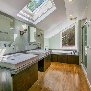 Trendy master medium tone wood floor and brown floor bathroom photo in Boston with flat-panel cabinets, dark wood cabinets, green walls, a vessel sink and gray countertops