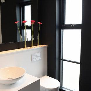 Immagine di una piccola stanza da bagno moderna con nessun'anta, ante bianche, WC sospeso, piastrelle bianche, piastrelle a specchio, pareti nere, parquet scuro, lavabo a bacinella, top in superficie solida, pavimento marrone, top bianco, un lavabo e mobile bagno incassato