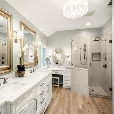 Corner shower - mid-sized transitional master gray tile and marble tile porcelain tile and brown floor corner shower idea in Dallas with recessed-panel cabinets, white cabinets, gray walls, an undermount sink, quartz countertops, a hinged shower door and white countertops