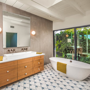 Photo of a midcentury ensuite bathroom in San Diego with flat-panel cabinets, medium wood cabinets, a freestanding bath, grey walls, ceramic flooring, a vessel sink, white floors and white worktops.