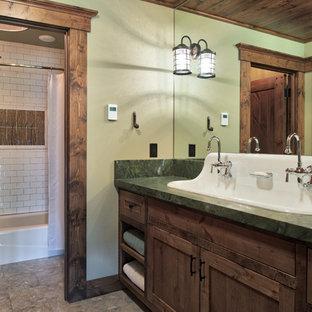 Imagen de cuarto de baño rural con armarios estilo shaker, puertas de armario de madera en tonos medios, bañera empotrada, combinación de ducha y bañera, baldosas y/o azulejos blancos, baldosas y/o azulejos de cemento, paredes verdes, lavabo de seno grande, suelo gris, ducha con cortina y encimeras verdes
