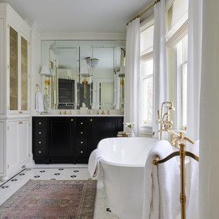 Modelo de cuarto de baño tradicional con armarios con paneles empotrados, puertas de armario negras, bañera exenta, paredes blancas, suelo con mosaicos de baldosas, lavabo bajoencimera, suelo blanco y encimeras blancas