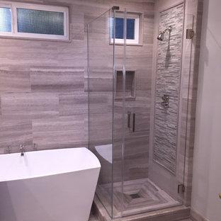 Esempio di una stanza da bagno tradizionale di medie dimensioni con top in pietra calcarea, vasca freestanding, doccia ad angolo, piastrelle grigie, piastrelle in pietra e pavimento in pietra calcarea