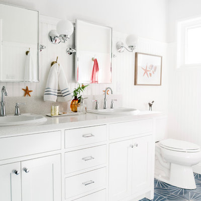 Example of a beach style blue floor bathroom design in Other with shaker cabinets, white cabinets, white walls, a drop-in sink and white countertops