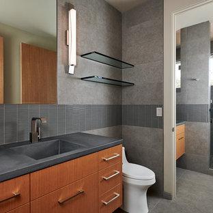 Idéer för att renovera ett mellanstort funkis grå grått en-suite badrum, med bänkskiva i betong, släta luckor, bruna skåp, grå kakel, grå väggar, ett integrerad handfat, grått golv och dusch med gångjärnsdörr