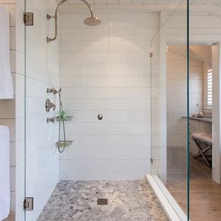 ボストンの広いビーチスタイルのおしゃれなマスターバスルーム (置き型浴槽、コーナー設置型シャワー、白いタイル、セラミックタイル、白い壁、淡色無垢フローリング) の写真
