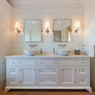 Foto di una grande stanza da bagno padronale stile marino con lavabo a bacinella, ante con riquadro incassato, ante bianche, top in marmo, pareti bianche e pavimento in legno massello medio