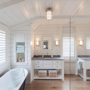 На фото: большая главная ванная комната в морском стиле с фасадами островного типа, белыми фасадами, столешницей из гранита, отдельно стоящей ванной, угловым душем, белой плиткой, керамической плиткой, белыми стенами, светлым паркетным полом и врезной раковиной