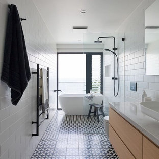 Photo of a contemporary master wet room bathroom in Sydney with a freestanding tub, a wall-mount toilet, white tile, subway tile, ceramic floors, marble benchtops, multi-coloured floor, an open shower, flat-panel cabinets, a vessel sink, light wood cabinets and multi-coloured benchtops.
