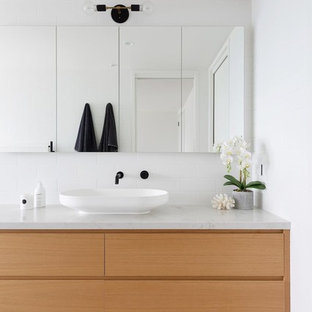 This is an example of a contemporary master bathroom in Sydney with a wall-mount toilet, white tile, subway tile, white walls, ceramic floors, marble benchtops, multi-coloured floor, flat-panel cabinets, a vessel sink, light wood cabinets and multi-coloured benchtops.