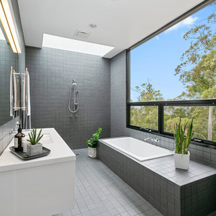 Inspiration for a large contemporary master bathroom in Hobart with a drop-in tub, gray tile, white benchtops, white cabinets, a curbless shower, an undermount sink, grey floor and an open shower.