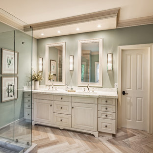 Inspiration for a timeless gray tile and travertine tile beige floor corner shower remodel in Other with raised-panel cabinets, an undermount sink, onyx countertops, a hinged shower door, white countertops, beige cabinets and green walls