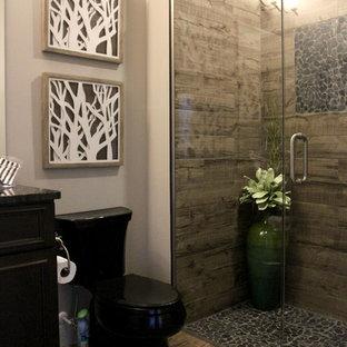 Diseño de cuarto de baño con ducha, rústico, de tamaño medio, con lavabo bajoencimera, armarios con paneles empotrados, puertas de armario de madera en tonos medios, encimera de granito, ducha a ras de suelo, sanitario de dos piezas, baldosas y/o azulejos marrones, baldosas y/o azulejos de cerámica, paredes grises y suelo de baldosas de cerámica