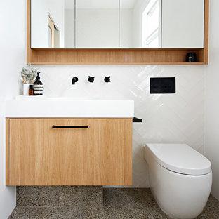 Ispirazione per una stanza da bagno con doccia minimal con ante in legno chiaro, vasca freestanding, doccia aperta, WC sospeso, piastrelle bianche, pareti bianche, pavimento alla veneziana, lavabo sottopiano, pavimento multicolore, doccia aperta e top bianco