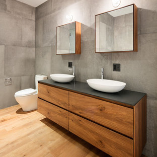 Example of a trendy 3/4 gray tile and cement tile medium tone wood floor and brown floor bathroom design in New York with flat-panel cabinets, medium tone wood cabinets, gray walls and a vessel sink