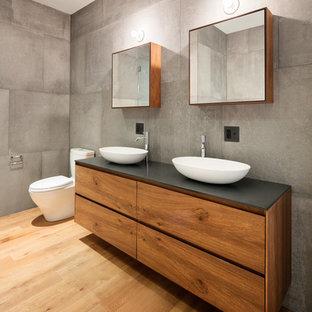 Ispirazione per una stanza da bagno con doccia design con ante lisce, ante in legno scuro, piastrelle grigie, piastrelle di cemento, pareti grigie, pavimento in legno massello medio, lavabo a bacinella e pavimento marrone