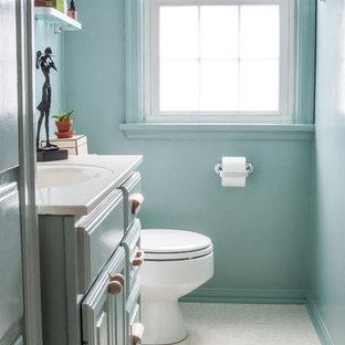 Esempio di una piccola stanza da bagno padronale minimal con ante con bugna sagomata, ante blu, vasca da incasso, vasca/doccia, WC a due pezzi, piastrelle bianche, pareti blu, pavimento in vinile, lavabo integrato e top in superficie solida