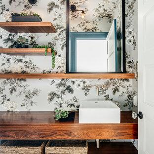 Inredning av ett nordiskt litet badrum, med öppna hyllor, skåp i mellenmörkt trä, flerfärgade väggar, ett fristående handfat, träbänkskiva och flerfärgat golv