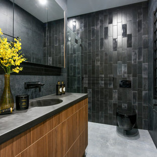 This is an example of a contemporary bathroom in Sydney with flat-panel cabinets, medium wood cabinets, a wall-mount toilet, black tile, an integrated sink, grey floor and grey benchtops.