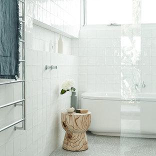 Esempio di una stanza da bagno minimal con vasca freestanding, doccia a filo pavimento, piastrelle bianche, pareti bianche, pavimento alla veneziana, pavimento grigio e doccia aperta