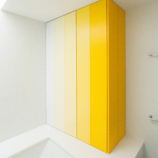 Idee per una stanza da bagno minimal con ante lisce, ante gialle, vasca sottopiano, piastrelle bianche, piastrelle in ceramica e top in quarzo composito