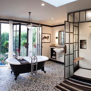 На фото: ванная комната в стиле лофт с ванной на ножках, белыми стенами, полом из цементной плитки и разноцветным полом с
