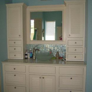 オーランドの大きいビーチスタイルのおしゃれなマスターバスルーム (ベッセル式洗面器、ルーバー扉のキャビネット、白いキャビネット、珪岩の洗面台、置き型浴槽、オープン型シャワー、青いタイル、ガラスタイル、青い壁、磁器タイルの床) の写真