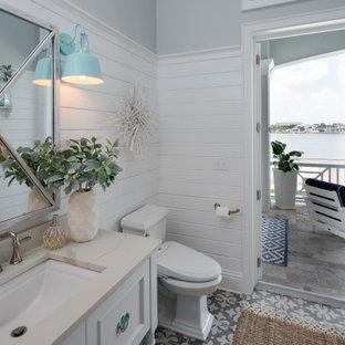 Foto på ett maritimt beige badrum, med luckor med infälld panel, vita skåp, grå väggar, ett undermonterad handfat och grått golv