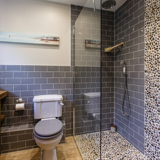 This is an example of a nautical bathroom in Cambridgeshire with freestanding cabinets, dark wood cabinets, a one-piece toilet, grey tiles, metro tiles, grey walls, ceramic flooring, a built-in sink, wooden worktops and an open shower.