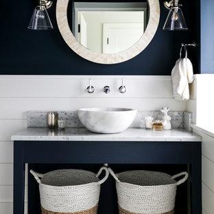 ロンドンのビーチスタイルのおしゃれな浴室 (青い壁、濃色無垢フローリング、ベッセル式洗面器、大理石の洗面台、茶色い床、白い洗面カウンター) の写真