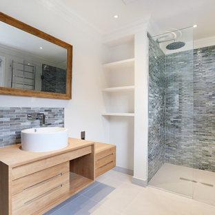 Идея дизайна: ванная комната в современном стиле с плоскими фасадами, светлыми деревянными фасадами, душем в нише, удлиненной плиткой, белыми стенами, душевой кабиной, настольной раковиной, столешницей из дерева, серой плиткой, душем с распашными дверями и бежевой столешницей