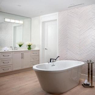 マイアミの広いビーチスタイルのおしゃれなマスターバスルーム (シェーカースタイル扉のキャビネット、ベージュのキャビネット、アルコーブ型シャワー、一体型トイレ、ベージュの壁、淡色無垢フローリング、アンダーカウンター洗面器、クオーツストーンの洗面台、茶色い床、開き戸のシャワー、白い洗面カウンター、洗面台2つ、造り付け洗面台、壁紙) の写真