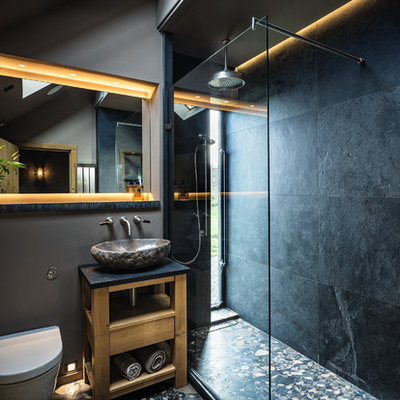 Inspiration for a coastal 3/4 black tile bathroom remodel in Cheshire with open cabinets, light wood cabinets, a wall-mount toilet, black walls and a vessel sink