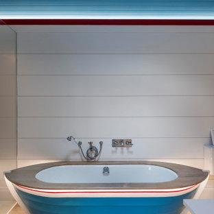 Maritim inredning av ett mellanstort vit vitt badrum för barn, med skåp i shakerstil, vita skåp, ett fristående badkar, en öppen dusch, vit kakel, vita väggar, mellanmörkt trägolv, ett väggmonterat handfat, bänkskiva i akrylsten, brunt golv och med dusch som är öppen