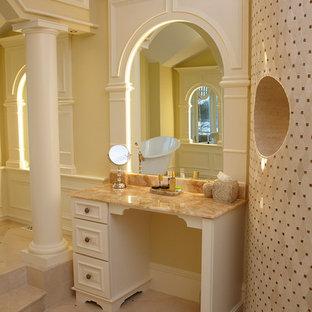 Ejemplo de cuarto de baño principal, tradicional, de tamaño medio, con armarios con paneles con relieve, puertas de armario beige, bañera con patas, ducha esquinera, sanitario de una pieza, baldosas y/o azulejos beige, baldosas y/o azulejos de mármol, paredes amarillas, suelo de mármol, lavabo bajoencimera, encimera de ónix, suelo beige y ducha abierta