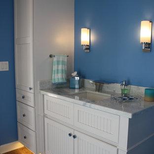 Esempio di una piccola stanza da bagno tropicale con ante a persiana, ante bianche, pareti blu, lavabo sottopiano, top in marmo, top blu e pavimento in gres porcellanato