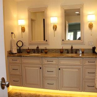Foto di una stanza da bagno padronale tropicale di medie dimensioni con ante con bugna sagomata, ante marroni, pareti beige, lavabo sottopiano, top in granito, top verde e pavimento in gres porcellanato